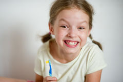 Funny girlie with pigtails brushing his teeth. Funny girl with pigtails brushing his teeth. She shows their clean white teeth with a cheerful smile stock photo