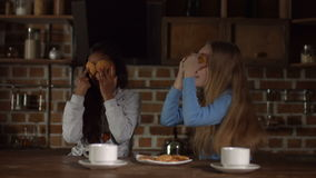 Funny girls covering eyes with cookies in kitchen. Smiling multiracial little girls covering their eyes with cookies during breakfast while sitting in moden stock video footage