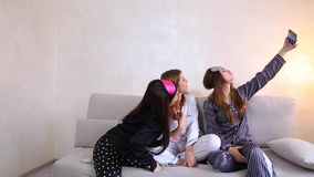 Funny girls doing selfie at home party, smiles on their faces and sitting on sofa background of light wall in room. stock video footage