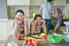 Funny girls are playing with food. They holds round pieces of cucumber where etes are and smile. Girls have a break stock images