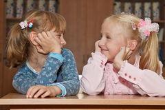 Funny girls in the school at the desk Stock Image