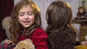 Funny girls sit back to back among toys and look at each other, slow motion stock footage