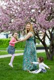 Funny girls walking on the lawn with her mother. Sisters play together with mom. maternal care. happy family royalty free stock image