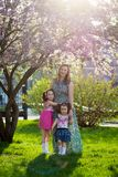 Funny girls walking on the lawn with her mother. Sisters play together with mom. maternal care. happy family stock image