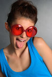 Funny glasses. A girl wearing funny glasses with her tongue sticking out Stock Image