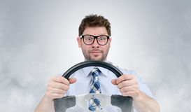 Funny in glasses bearded man with a steering wheel in smoke Royalty Free Stock Photography