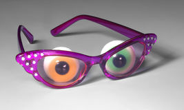 Funny glasses. With eyeballs in grey back Royalty Free Stock Photos