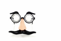 Funny glasses. A pair of funny groucho marx glasses set against a white background stock image