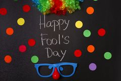 Funny glasses, rainbow wig and phrase. `Happy fool`s day` on chalkboard. 1st April celebration Stock Photography
