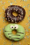 Funny glazed donuts on gold background Royalty Free Stock Photos