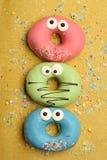 Funny glazed donuts on gold background Stock Photo