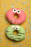 Funny glazed donuts on gold background Royalty Free Stock Photography