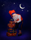 Funny gnome with gift at the night Royalty Free Stock Photos