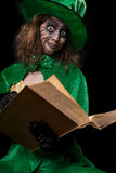 Funny goblin girl is reading from a book, concept fairytales and royalty free stock photography