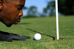 Funny golf. A male golfer is blowing the golf ball into the hole Royalty Free Stock Images