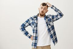 Funny good-looking caucasian male student with beard in blue plaid shirt, preparing for exam, scratching head, looking. Confused and clueless, having no idea Royalty Free Stock Photo