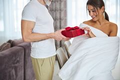 Funny gorgeous female wrapped in quilt taking present red box in cozy apartment