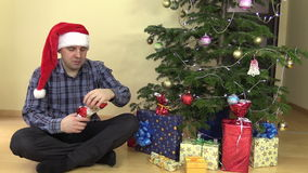 Funny gourmand man lick lips eat chocolate Christmas Santa. Funny gourmand man lick lips while prepare to eat chocolate Christmas Santa near fir tree with toys stock video