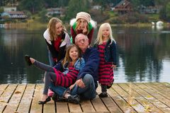 Funny Grandfather with a group of kids. A funny Grandfather with a group of kids making silly faces at a quiet lake outside royalty free stock photos