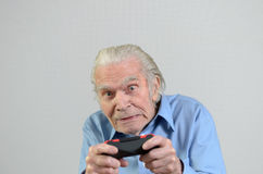 Funny grandfather playing a video game on console Stock Images