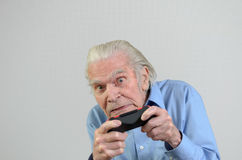 Funny grandfather playing a video game on console Stock Photography
