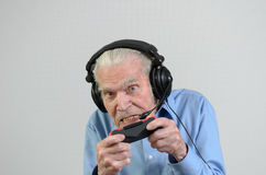 Funny grandfather playing a video game on console. Funny elderly man or grandfather using black headset with headphones and microphone while playing a video game Royalty Free Stock Images