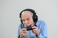 Funny grandfather playing a video game on console. Funny elderly man or grandfather using black headset with headphones and microphone while playing a video game Stock Photography