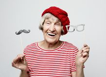 Funny grandmother with fake mustache and glasses, laughs and prepares for party over grey background. Lifestyle and people concept: funny grandmother with fake stock photos