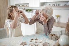 Cheerful girl and granny having fun with cookies Stock Photos
