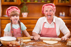 Funny grandmother and little granddaughter lollygag in the kitch Stock Photos