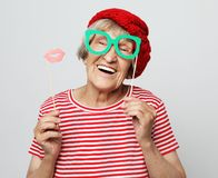 Funny grandmother wearing red clothes holding falce glasses and ready for party. Lifestyle, people and party concept: funny grandmother wearing red clothes royalty free stock image