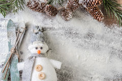 Funny gray and white snowman with skis. Gray and white snowman with a pair of skis and a snowy fir branch with pine cones on a white background Royalty Free Stock Photo