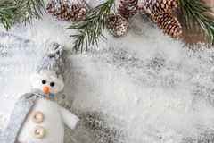Funny gray and white snowman. Gray and white snowman and a snowy fir branch with pine cones on a snow background Royalty Free Stock Image