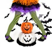 Funny green black Striped legs of a little girl with halloween costume of a witch with witch shoes and smiley halloween pumpkin stock image
