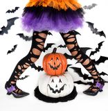 Funny black legs of a little girl with halloween costume of a witch with witch shoes and smiley halloween pumpkin royalty free stock image