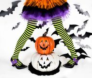 Funny green black Striped legs of a little girl with halloween costume of a witch with witch shoes and smiley halloween pumpkin stock photo