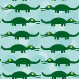 Funny green crocodile Seamless pattern with cute animal on a blu Royalty Free Stock Photo