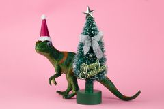 Funny green dinosaur toy. In little santa claus hat near little christmas tree on pastel pink background stock photos
