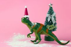 Funny green dinosaur toy. In little santa claus hat near little christmas tree on pastel pink background royalty free stock photo
