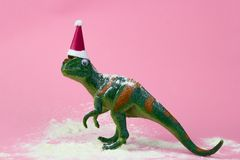 Funny green dinosaur toy. In little santa claus hat and snow on pastel pink background royalty free stock photo