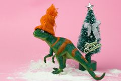 Funny green dinosaur toy. In littleorange knitted hat near little christmas tree on pastel pink background stock photo