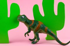 Plastic funny green dinosaur. Funny green dinosaur toy and paper craft cacti on pastel pink background stock photography