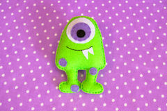 Funny green monster felt on purple fabric polka dot pattern. Sewing concept stock photo