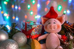 Funny greeting card with new year 2019. Pink pig with xmas balls and gift on background with illumination royalty free stock photography