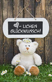 Funny greeting card with teddy bear and a wooden white sign with Stock Photography