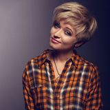 Funny grimacing woman with short blond hair style posing in yell. Ow Halloween shirt on grey background. Closeup toned color portrait Royalty Free Stock Images