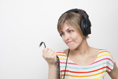 Funny grimacing young woman with headphones Stock Images