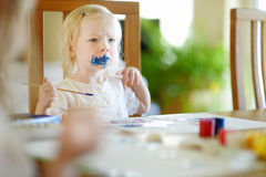 Funny grimy toddler girl painting Stock Photography
