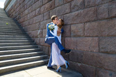Funny groom and bride hugging near stairs in town Royalty Free Stock Photography