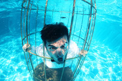 Funny groom underwater in a bird cage Stock Photos
